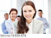 Купить «Успешная деловая женщина улыбается в многолюдном офисе», фото № 4939474, снято 16 июля 2011 г. (c) Syda Productions / Фотобанк Лори