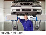 Купить «Улыбающийся автомеханик под автомобилем на подъемнике», фото № 4951894, снято 17 апреля 2012 г. (c) Wavebreak Media / Фотобанк Лори