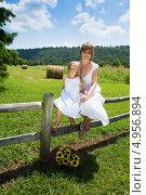Купить «Счастливые мама с  дочкой в белых платьях сидят на заборе», фото № 4956894, снято 14 августа 2013 г. (c) Ирина Кожемякина / Фотобанк Лори