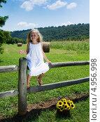 Купить «Счастливая пятилетняя девочка в белом платье что-то рассказывает сидя на  заборе», фото № 4956998, снято 14 августа 2013 г. (c) Ирина Кожемякина / Фотобанк Лори