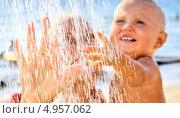 Купить «Мама с малышом под струей воды на пляже», фото № 4957062, снято 20 ноября 2019 г. (c) Светлана Кузнецова / Фотобанк Лори