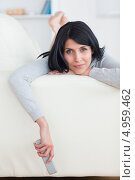Купить «Девушка лежит на диване на животе, свесив с дивана руку с пультом от телевизора», фото № 4959462, снято 29 марта 2012 г. (c) Wavebreak Media / Фотобанк Лори
