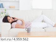 Купить «Улыбающаяся девушка говорит по мобильному телефону лежа на спине на диване», фото № 4959562, снято 29 марта 2012 г. (c) Wavebreak Media / Фотобанк Лори
