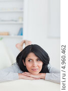Купить «Девушка латиноамериканской внешности лежит на животе на диване, положив голову на руки», фото № 4960462, снято 29 марта 2012 г. (c) Wavebreak Media / Фотобанк Лори