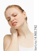 Купить «Молодая женщина держится за шею, сморщившись от боли», фото № 4960742, снято 5 апреля 2012 г. (c) Wavebreak Media / Фотобанк Лори