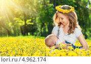 Купить «Мама в венке кормит малыша в поле среди цветов», фото № 4962174, снято 3 июня 2013 г. (c) Евгений Атаманенко / Фотобанк Лори