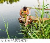 Девушка в купальнике с букетом кувшинок сидит на берегу озера. Стоковое фото, фотограф Антон Куделин / Фотобанк Лори