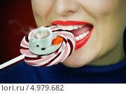 Женщина кусает леденец, на котором стоит чашка с кофе. Стоковое фото, фотограф O.Guerro / Фотобанк Лори