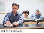 Купить «Взрослый мужчина сидит за столом во время лекции и делает записи», фото № 4984726, снято 12 июля 2012 г. (c) Wavebreak Media / Фотобанк Лори