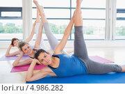 Купить «Три девушки выполняют упражнения на матах в спортзале с большими окнами», фото № 4986282, снято 11 июля 2012 г. (c) Wavebreak Media / Фотобанк Лори