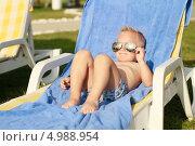 Маленький мальчик в солнцезащитных очках отдыхает на шезлонге. Стоковое фото, фотограф Tanya Lomakivska / Фотобанк Лори