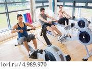 Купить «Трое людей занимаются на тренажерах типа рычажная тяга в спортзале с большими окнами», фото № 4989970, снято 11 июля 2012 г. (c) Wavebreak Media / Фотобанк Лори