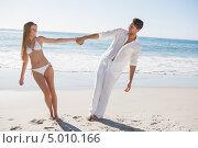 молодая влюбленная пара гуляет вместе по тропическому пляжу и держатся за руки. Стоковое фото, агентство Wavebreak Media / Фотобанк Лори