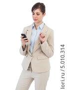 Купить «деловая девушка в офисной одежде держит телефон в руке», фото № 5010314, снято 29 марта 2013 г. (c) Wavebreak Media / Фотобанк Лори