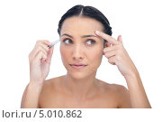 Купить «девушка выщипывает себе брови и смотрит в сторону», фото № 5010862, снято 25 мая 2013 г. (c) Wavebreak Media / Фотобанк Лори