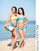 Две девушки в купальниках с надувным мячом на берегу моря. Стоковое фото, фотограф Syda Productions / Фотобанк Лори