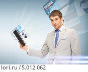 Молодой человек читает последние новости на планшетном компьютере. Стоковое фото, фотограф Syda Productions / Фотобанк Лори