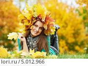 Купить «Девушка в венке из жёлтых кленовых листьев лежит на газоне», фото № 5012966, снято 4 октября 2011 г. (c) Дмитрий Калиновский / Фотобанк Лори