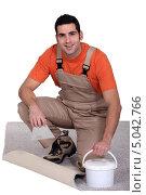 Рабочий с ведерком с клеем укладывает ковровое покрытие. Стоковое фото, фотограф Phovoir Images / Фотобанк Лори
