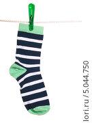 Купить «Полосатый носок, висящий на бельевой веревке», фото № 5044750, снято 16 марта 2012 г. (c) Paleka / Фотобанк Лори