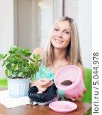 Купить «Девушка пересаживает растение в цветочный горшок», фото № 5044978, снято 15 декабря 2012 г. (c) Яков Филимонов / Фотобанк Лори