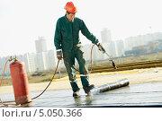Рабочий ремонтирует крышу на фоне новостроек. Стоковое фото, фотограф Дмитрий Калиновский / Фотобанк Лори