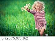 Веселая девочка с деревянным самолетиком в руке бежит по зеленой траве. Стоковое фото, фотограф Raev Denis / Фотобанк Лори