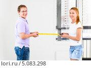 Купить «Мужчина и женщина измеряют рулеткой новую квартиру», фото № 5083298, снято 9 сентября 2013 г. (c) Сергей Петерман / Фотобанк Лори