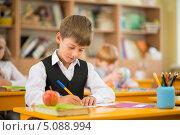 Купить «Ученик на уроке. Мальчик сидит за партой и пишет ручкой», фото № 5088994, снято 14 августа 2013 г. (c) Andrejs Pidjass / Фотобанк Лори