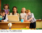 Купить «Учительница и ученики на фоне школьной доски. Женщина сидит за столом перед ноутбуком, дети стоят рядом», фото № 5089034, снято 14 августа 2013 г. (c) Andrejs Pidjass / Фотобанк Лори