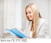 Купить «Молодая женщина увлеченно читает книгу», фото № 5111102, снято 30 марта 2013 г. (c) Syda Productions / Фотобанк Лори