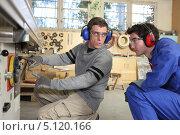 Купить «Опытный рабочий рассказывает молодому коллеге об устройстве станка», фото № 5120166, снято 5 февраля 2010 г. (c) Phovoir Images / Фотобанк Лори