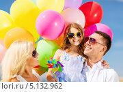 Счастливая семья со связкой ярких воздушных шаров под голубым небом. Стоковое фото, фотограф Syda Productions / Фотобанк Лори
