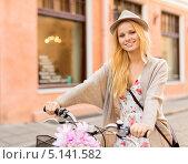 Купить «Привлекательная девушка едет на велосипеде по улице», фото № 5141582, снято 6 сентября 2013 г. (c) Syda Productions / Фотобанк Лори