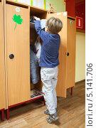 Мальчик убирает вещи в шкафчик в детском саду. Стоковое фото, фотограф Юлия Кузнецова / Фотобанк Лори