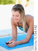 Купить «Девушка читает смс, лежа на полотенце возле бассейна», фото № 5154142, снято 20 сентября 2010 г. (c) Phovoir Images / Фотобанк Лори