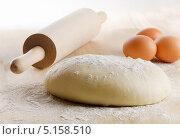 Купить «Тесто, три яйца и скалка на деревянном столе», фото № 5158510, снято 11 октября 2013 г. (c) Tatjana Baibakova / Фотобанк Лори