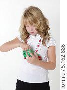 Девочка достает подарок из упаковки. Стоковое фото, фотограф Olga Taranik / Фотобанк Лори