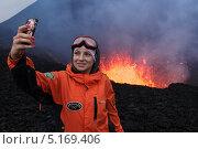 Девушка-турист фотографируется на фоне извержения вулкана Плоский Толбачик на Камчатке (2013 год). Редакционное фото, фотограф А. А. Пирагис / Фотобанк Лори