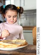 Купить «Девочка ест блины на кухне», фото № 5172986, снято 14 января 2010 г. (c) Phovoir Images / Фотобанк Лори