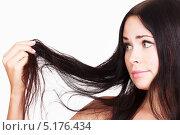 Купить «Девушка-брюнетка смотрит на свои кончики волос», фото № 5176434, снято 17 октября 2013 г. (c) Nobilior / Фотобанк Лори