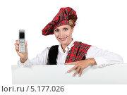 Купить «Улыбающаяся девушка в шотландском костюме с мобильным телефоном за баннером», фото № 5177026, снято 14 июня 2010 г. (c) Phovoir Images / Фотобанк Лори