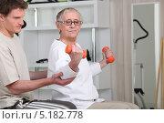 Купить «Старая женщина занимается с гантелями под руководством тренера», фото № 5182778, снято 13 апреля 2010 г. (c) Phovoir Images / Фотобанк Лори