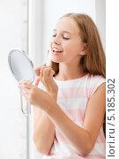 Купить «Девочка наносит блеск на губы», фото № 5185302, снято 7 августа 2013 г. (c) Syda Productions / Фотобанк Лори