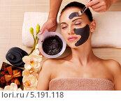 Косметолог наносит кистью черную маску на лицо девушки. Процедура в спа-салоне. Стоковое фото, фотограф Валуа Виталий / Фотобанк Лори