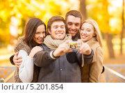 Купить «Группа друзей фотографируется на парке осенним днем», фото № 5201854, снято 5 октября 2013 г. (c) Syda Productions / Фотобанк Лори