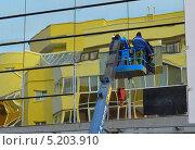 Строители поднимают на кране-подъемнике облицовочное зеркало (2013 год). Редакционное фото, фотограф Евгений Волвенко / Фотобанк Лори