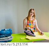 Купить «Молодая женщина гладит утюгом одежду», фото № 5213114, снято 14 августа 2013 г. (c) Валерия Потапова / Фотобанк Лори