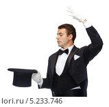 Купить «Молодой трюкач показывает фокус с шляпой на белом фоне», фото № 5233746, снято 12 сентября 2013 г. (c) Syda Productions / Фотобанк Лори