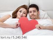 Купить «молодая пара лежит в кровати с бумажным сердцем в руках», фото № 5240546, снято 21 апреля 2013 г. (c) Андрей Попов / Фотобанк Лори